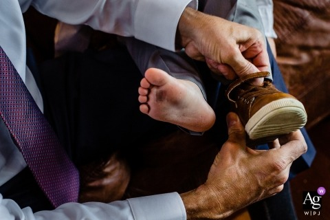 Rangely Maine wedding photographer: The father of the bride helps his grandson get into his wedding day shoes but doesn't notice his dirty feet