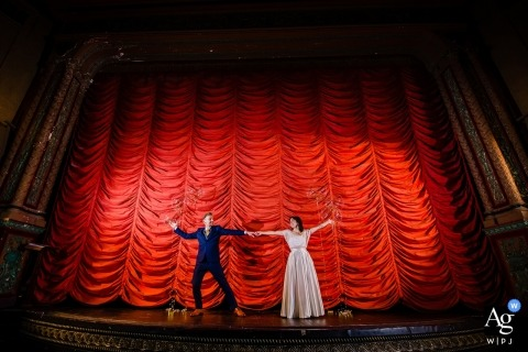 music box theatre wedding pictures - bride and groom portraits on the stage with a big red curtain.