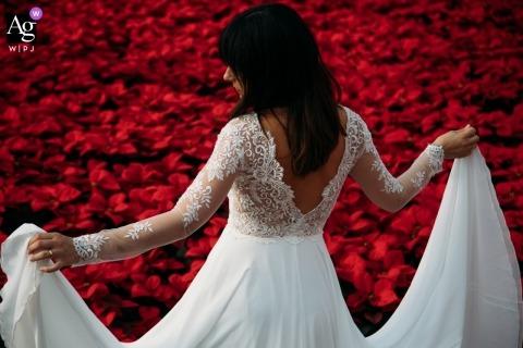 Dansende de bruidfoto van Sicilië met witte kleding en rode bloemachtergrond