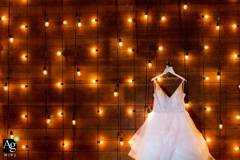 Rhode Island reception venue photo of the dress hanging on a wall covered in lights