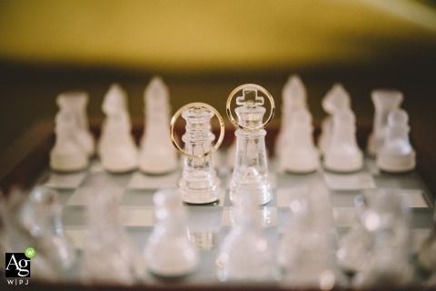 Attica wedding photo from the clients home | Detail photography of rings on a chessboard, on the queen and king pawns