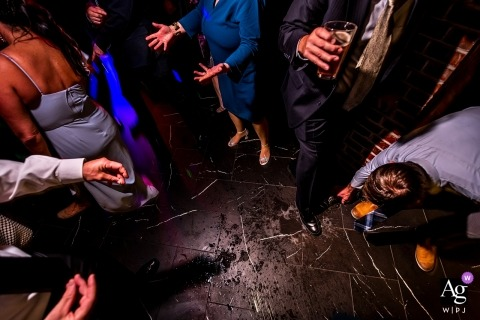 Ironworks (Denver, CO) venue photography - Wedding guest dropping a glass on the dance floor