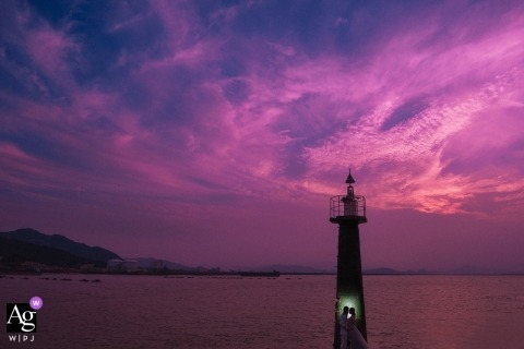 Fujian Island Groom and bride posing under the lighthouse for wedding portraits at sunset