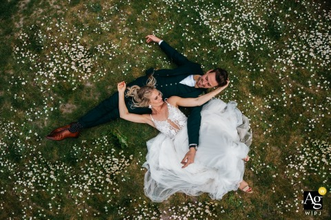 Flanders bride and groom are laying in the grass, in between flowers during creative portrait session.