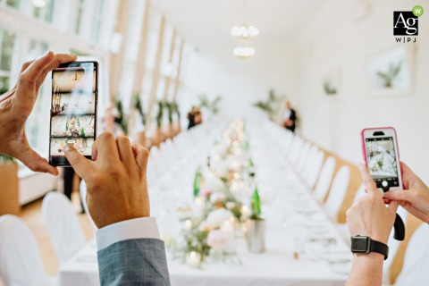 Europahaus Vienna Wedding guests taking photos. | Detail photography of camera phones and the reception table