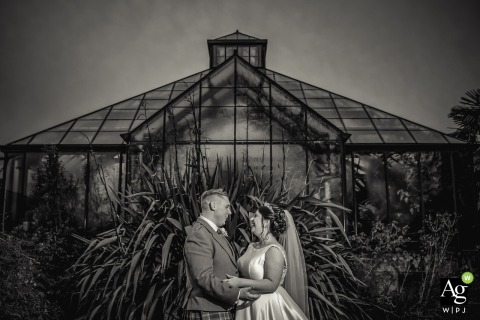 Scotland Botanic gardens portrait photo. Bride & groom in front of glasshouse in black and white photography.