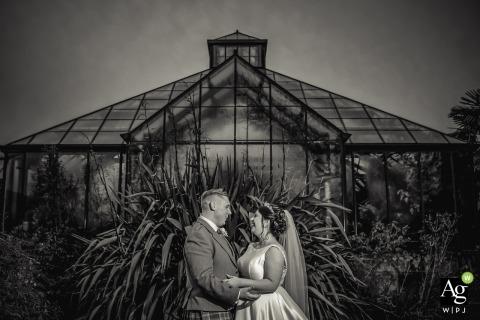 Portretfoto van de botanische tuinen van Schotland. Bruid & bruidegom voor kas in zwart-witfotografie.