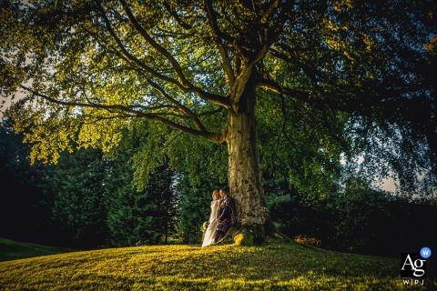 """Ontvangstlocatie in Schotland Foto van de bruid en bruidegom die bij zonsondergang """"boom leunt""""."""