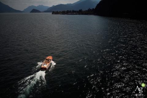 Italië comomeer trouwdag fotografie | Paarportret van een drone op een boot op het water