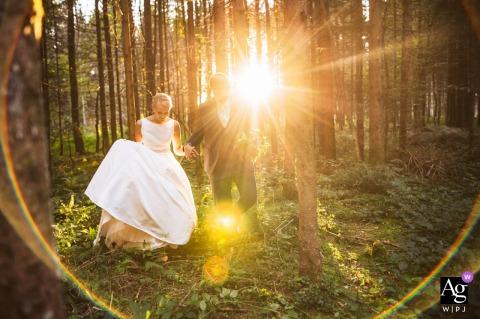 Slovenië huwelijksportret in het bos | Lopend in de richting van de fotograaf schijnt dan een sterke zon door het bos