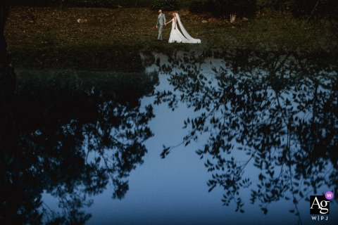 Santa Maria - Rio Grande do Sul portrait of the bride and groom walking with reflection of sky and trees.