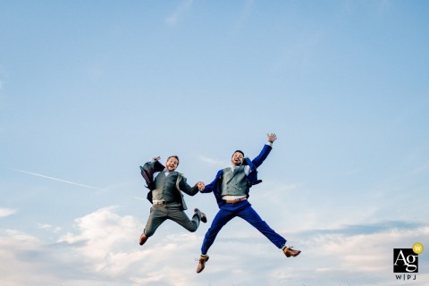 Linganore Winery wedding portraits | Jumping in the air against the blue sky and clouds.