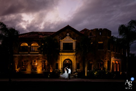 Stormy sunset wedding portrait using the uplighting on the house for ambient light at the Howey Mansion, Orlando, Florida
