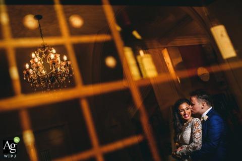 Hedsor House fine art mariage portrait image du couple bénéficiant d'un moment de calme reflété dans une fenêtre en miroir