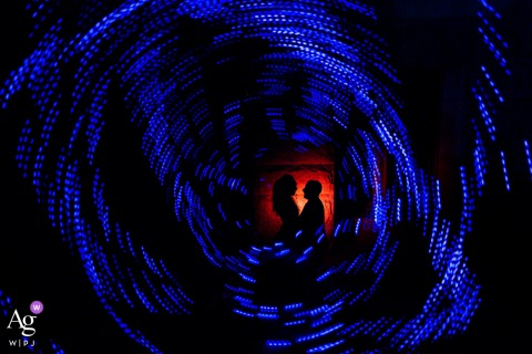 A playful and creative night portrait using christmas lights the couple's silhouette at the Pioneer Museum, Colorado Springs, Colorado