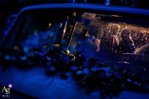 Trouwfoto van Winter Park, CO van het stel dat zich verstopt voor de regen in een oude Volkswagen-bus om hun kleine bruiloft af te sluiten