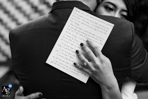 Ho Chi Minh artistic wedding photo of the bride hugging the groom holding a letter in Vietnam