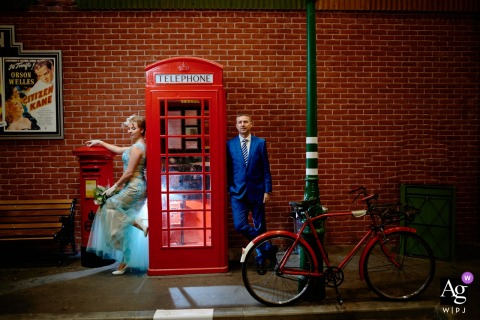 Bride and groom portrait standing next to a vintage UK red phone booth