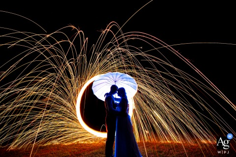 A nighttime wedding portrait of bride and groom with steel wool in Lincoln, NE at a private residence