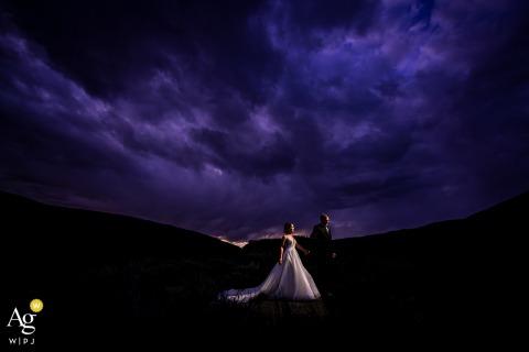 Ein Braut- und Bräutigamporträt von Camp Hale (Red Cliff, CO) unter lila Sonnenuntergang
