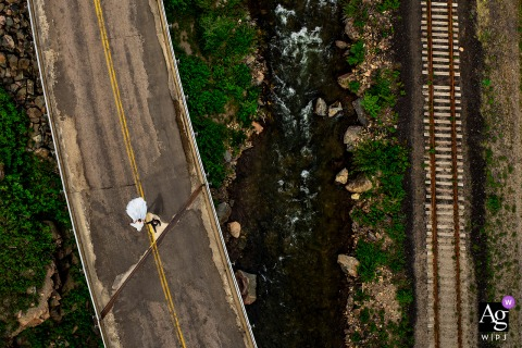 Aerial photo of bride and groom walking down road at Camp Hale in Red Cliff, CO