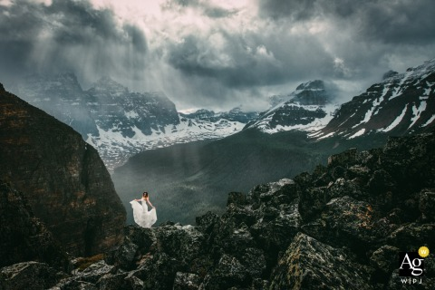 Moraine Lake, AB, Canada Bride holding her wedding dress in the mountains