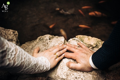 Church of Saint Albert Chmielowski, Lodz, Poland fine art wedding detail photography close-up of the hands of the bride and groom leaning against the edge of the pond