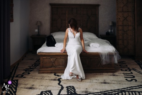 Best Western Hotel artistic wedding photo of a Lodzkie Podklasztorze, Sulejow, Poland Bride sitting on the bed in her room