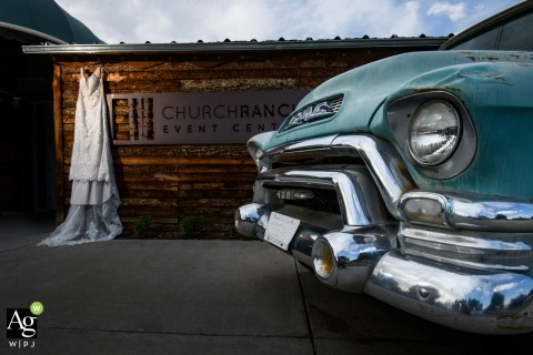 Church Ranch Event Center, Westminster, CO fine art wedding detail photography of the Wedding dress hanging near the venue entrance with a vintage auto
