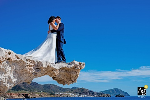 Cabo de Gata wedding portrait of the bride and groom standing on a rock ledge