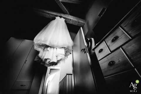 Uhingen fine art wedding detail photography picture from a low angle of the wedding dress hanging and waiting for the bride