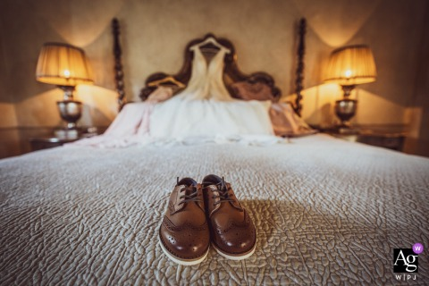 Borgo Santo Pietro wedding detail image of little shoes of the Bride's son with the wedding dress in the background