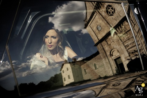 Portrait of the bride while she sits in a car outside of Antico Casale Urbani