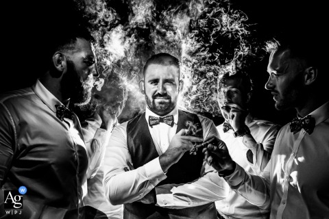 Portrait of the groom smoking with his groomsmen in this black and white image