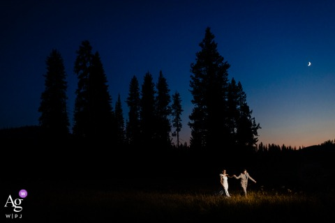 Lolo Pass, Idaho bride/groom portrait at dusk with a light, some stars and some trees