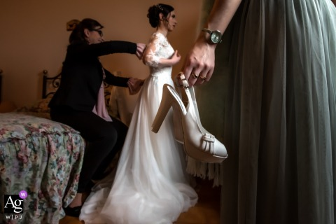 The two witnesses help the bride to complete the dressing, dress worn and shoes ready for the Italy wedding