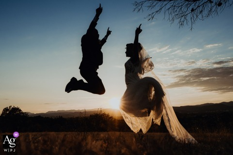 The bride and groom jump in the air in front of the sunset at Comptoir Saint-Hilaire