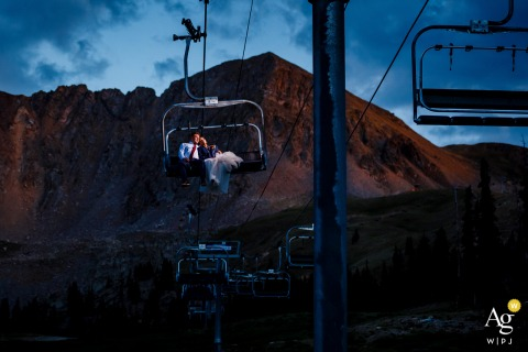 The newlyweds ride the chairlift down at sunset from their Arapahoe Basin Wedding.