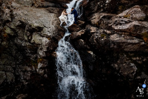 The bride & groom crossing a waterfall shortly after their elopement at Blue Lakes, Breckenridge, Colorado