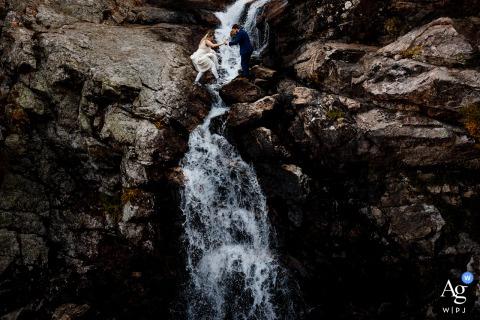Die Braut und der Bräutigam überqueren kurz nach ihrer Flucht einen Wasserfall in Blue Lakes, Breckenridge, Colorado