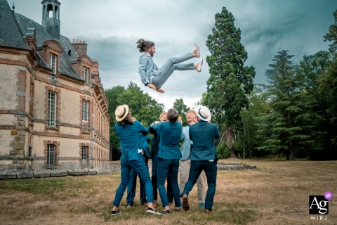 Château de Neuville, France wedding image of the groom being thrown in the air from the men