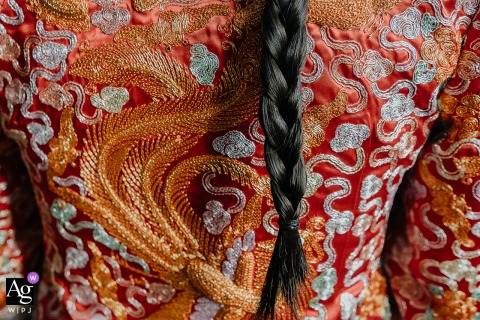 A detail image of the bride's clothing and braided hair at her Chinese wedding