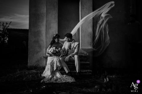 Villa Catignano portrait de mariage du couple assis au pied d'une colonne tandis que le vent vole le voile les enveloppant