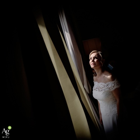 Villa Necchi alla Portalupa, Gambolò, Pavia fine art wedding portrait image of the bride at the window checking the weather before leaving her room