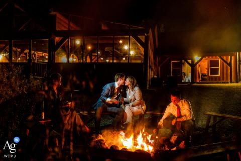 Braut und Bräutigam küssen sich, nachdem sie am Lagerfeuer auf der Piney River Ranch in Vail, CO, einen Geruch genossen haben