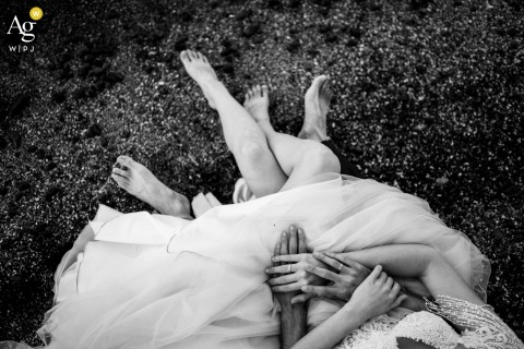 Tsarevo, Bulgaria Wedding rings detail image with her dress and bare feet on the grass