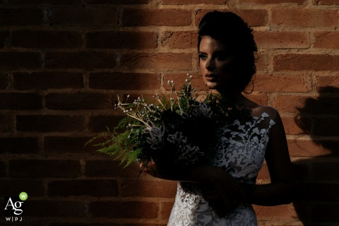 Haras Albar creative wedding day portrait showing the brides look as she holds her flowers in the sunlight against a brick wall