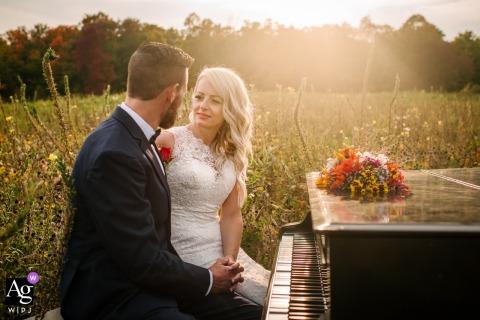 Tamworth, Ontario wedding portrait of the bride and groom sitting at a grand piano in the meadows