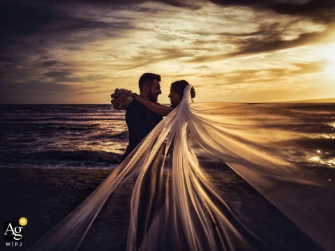 Portofino portrait of the bride and groom at sunset by the water with her long veil