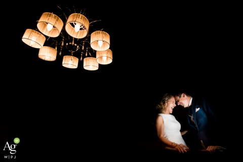 Geneva artistic wedding couple portrait of A couple laughing with a great light overhead on a dark background